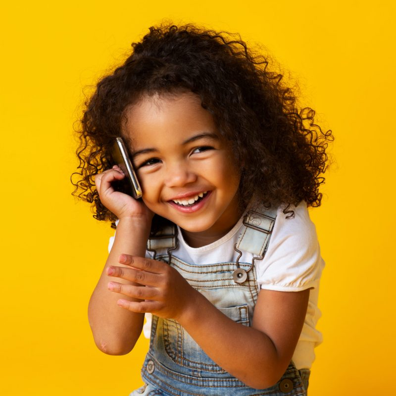 Cute afro girl talking on cellphone and smiling on yellow studio background